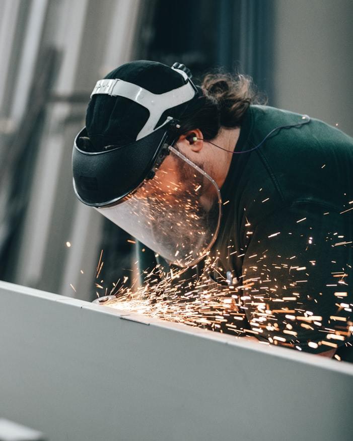 Homem utilizando viseira de proteção ocular enquanto opera um barbequim