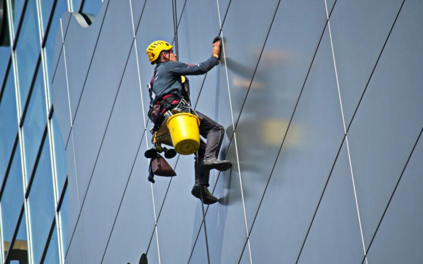 Homem utilizando arnês de segurança enquanto faz trabalhos em altura